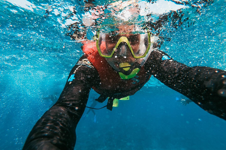 Snorkeler wearing rashguard and snorkel vest