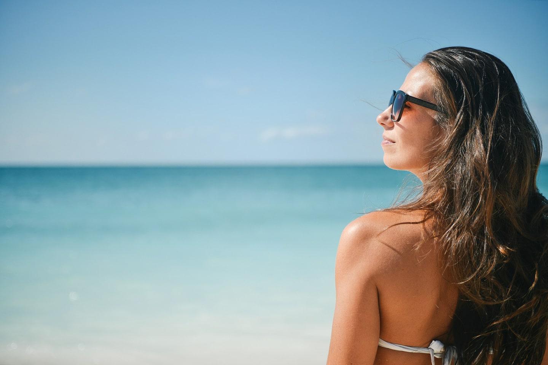 Girl wears sunglasses on the beach