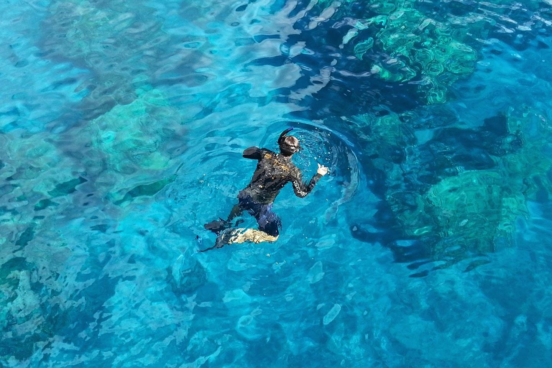 Man is snorkeling in UV T-shirt