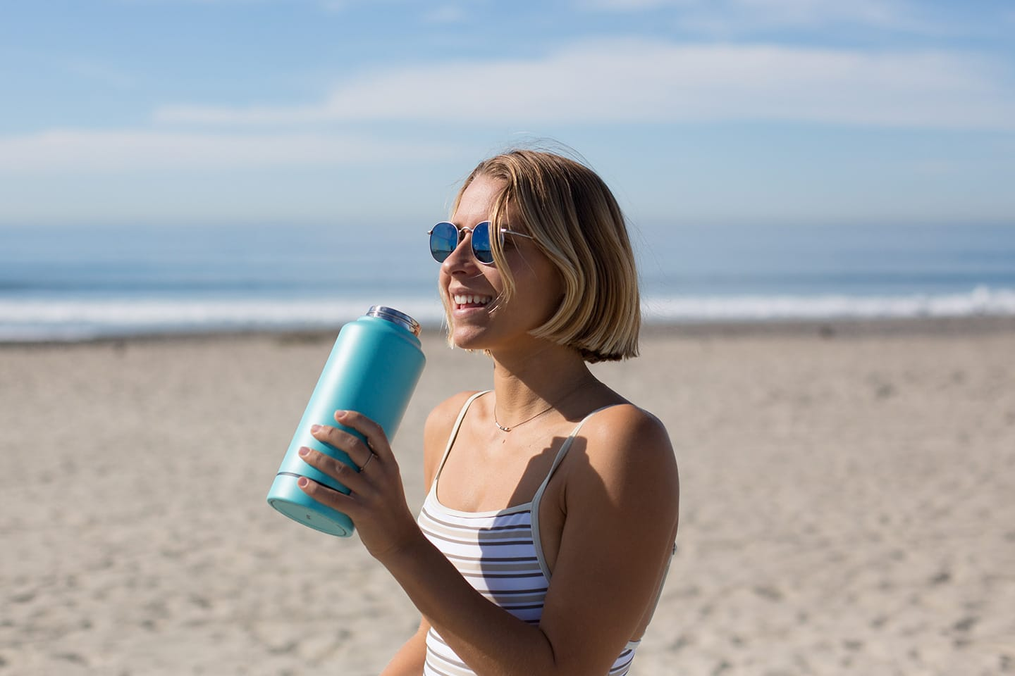 Woman with metal water bottle at the beach