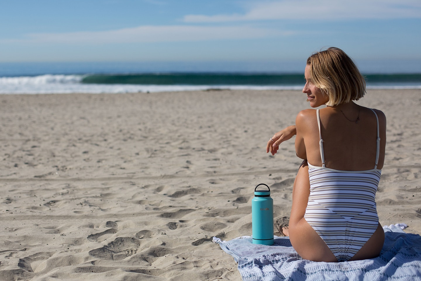 Woman on the beach with reusable water bottle