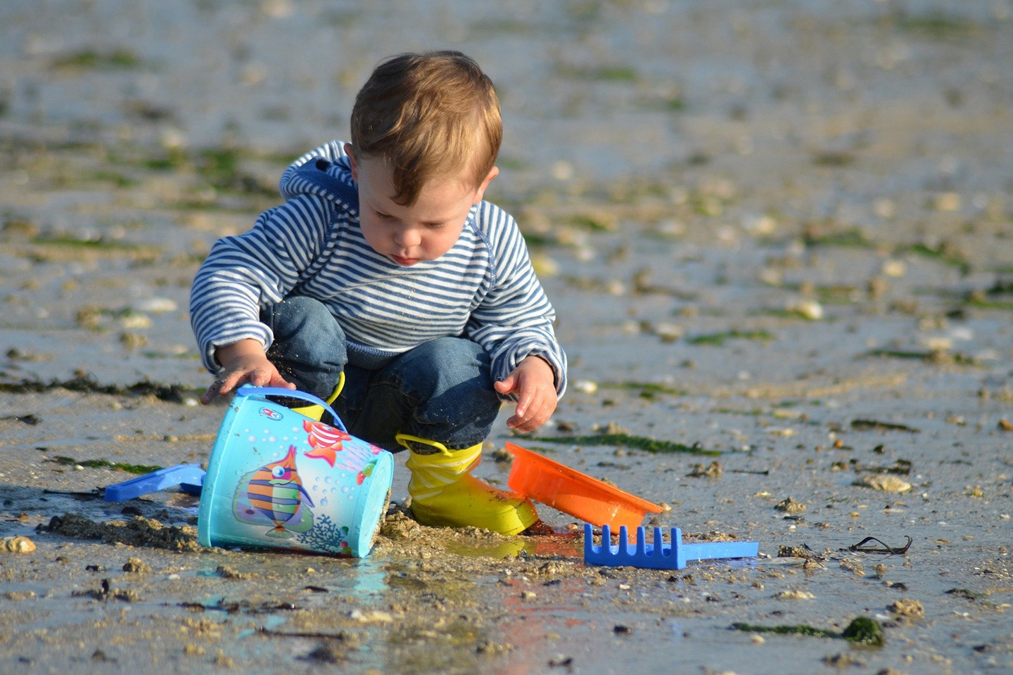 kid is playing on the beach with toys