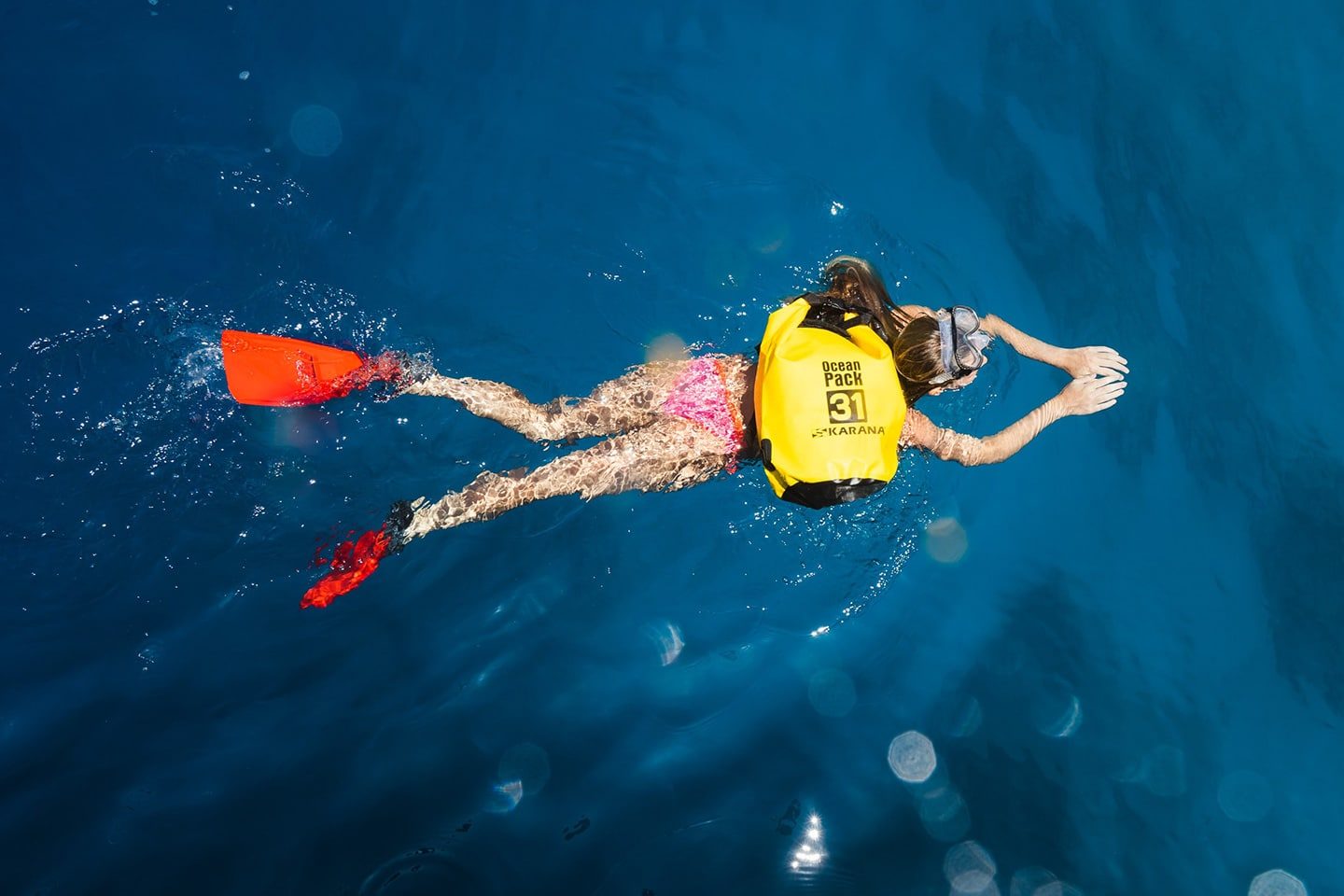 girl is snorkeling with dry bag