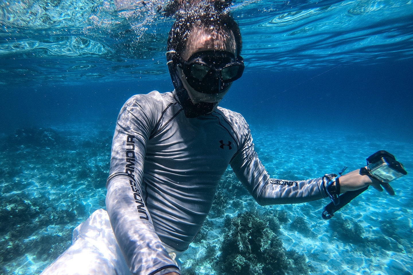 Man is snorkeling wearing rash guard top