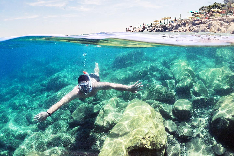 man swimming underwater wearing snorkeling mask