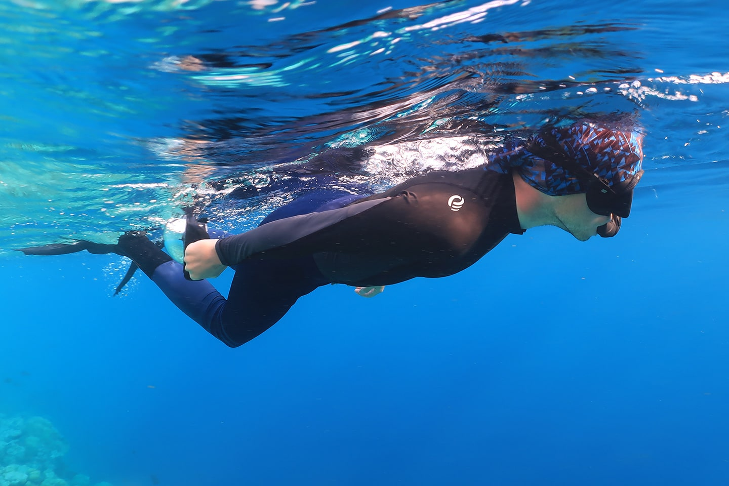 man wearing full body uv protection rash guard while snorkeling
