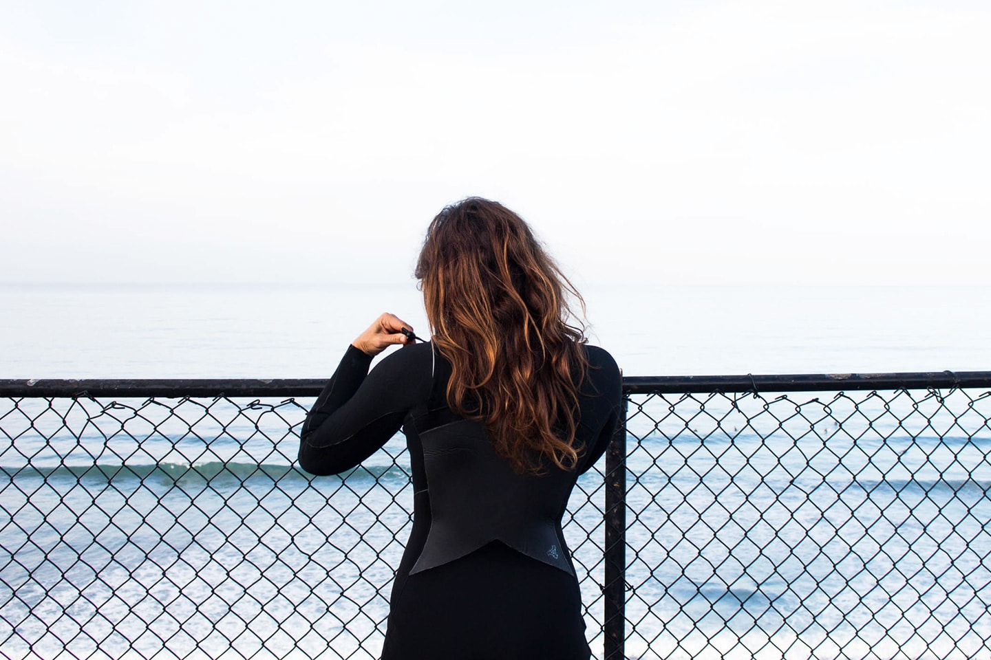 women in wetsuit next to the ocean