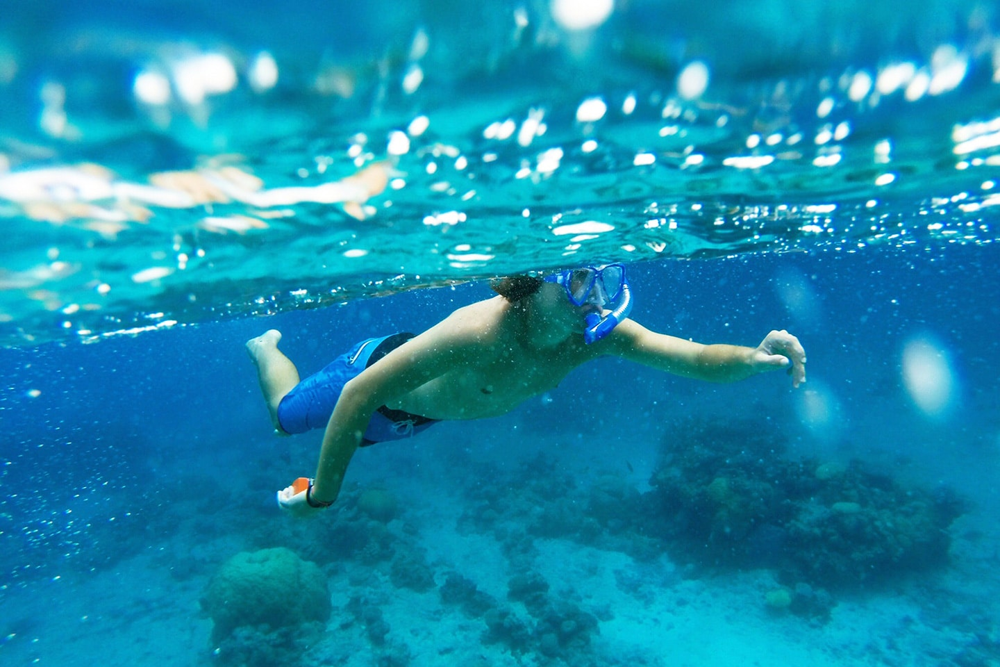 Boy is snorkeling wearing mask and snorkel