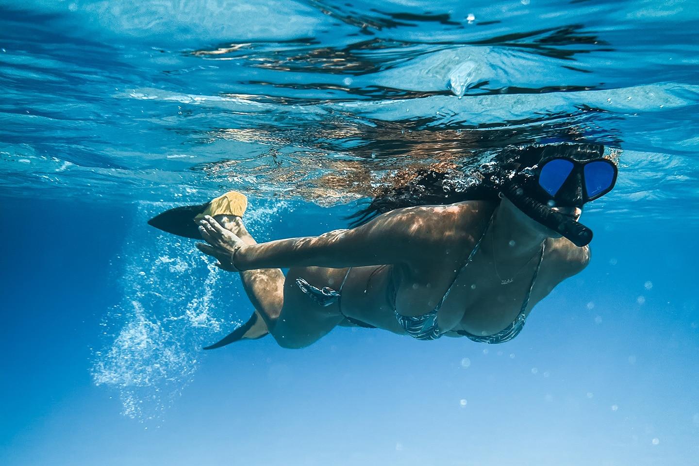 girl snorkeling wearing a snorkel set